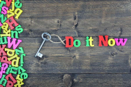 Do it now word on wooden table