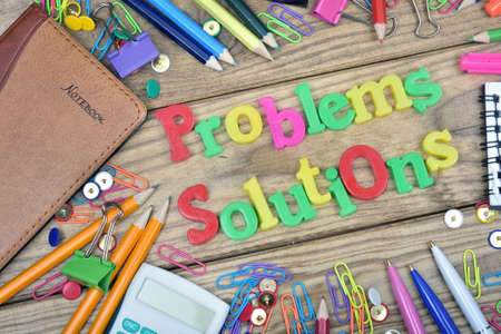 problems solutions: Problems Solutions words and office tools on wooden table
