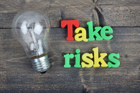 risky innovation: Take risks word on wooden table