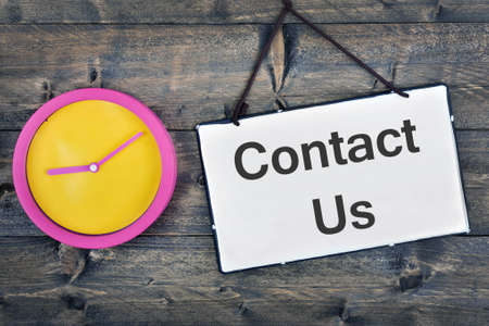 contact us sign: Contact  us sign and clock on wooden table
