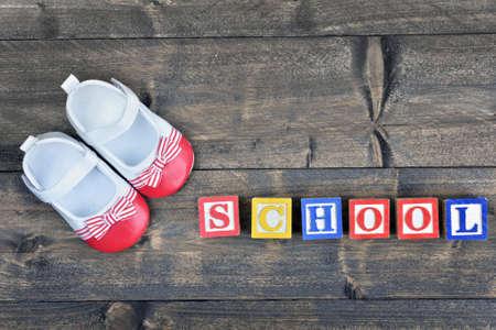 zapatos escolares: los zapatos del ni�o y escuela de la palabra en la mesa de madera Foto de archivo