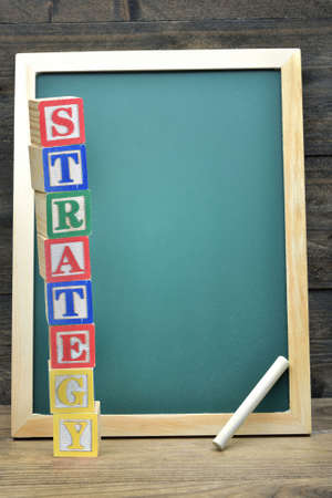 school strategy: School board and word Strategy on wooden table Stock Photo