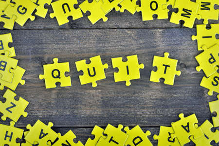 Puzzle pieces with word Quit Stock Photo