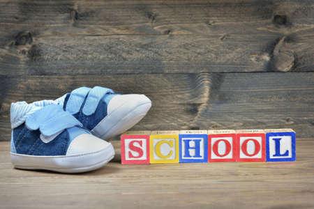 zapatos escolares: los zapatos del niño y escuela de la palabra en la mesa de madera Foto de archivo