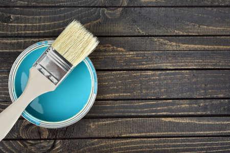 paint bucket: Paint bucket and brush on wooden table