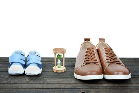 Grow up concept with kid shoes and business shoes on wooden floor Stock Photo