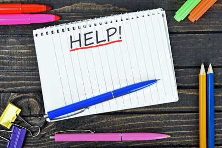 stationery needs: Help text on notepad and office tools on wooden table