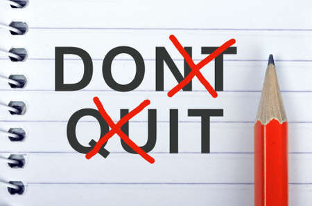 Dont quit text on notepad and red pencil Stock Photo