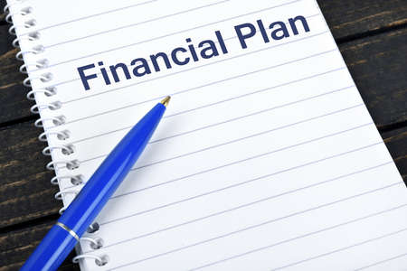 blue pen: Financial Plan text on notepad and blue pen