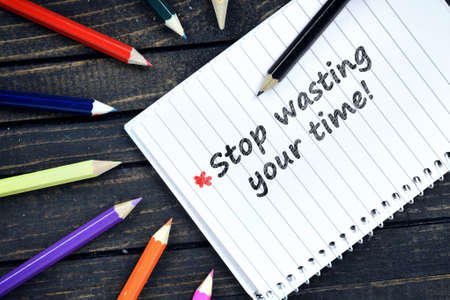 wasting: Stop wasting your time text on notepad and colorful pencils