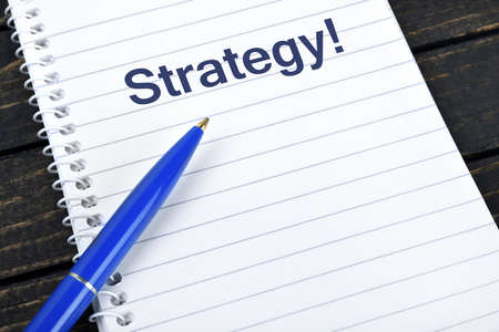 blue pen: Strategy text on notepad and blue pen Stock Photo
