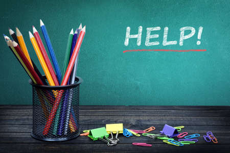 stationery needs: Help text on green board and group of pencils Stock Photo