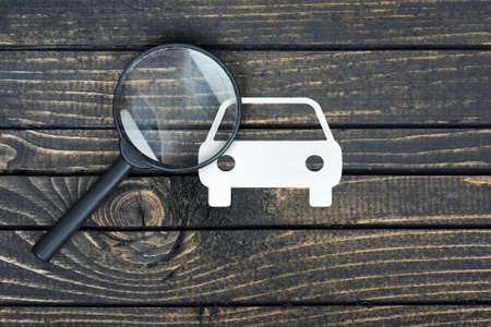car retailer: Magnifying glass paper house on wooden table