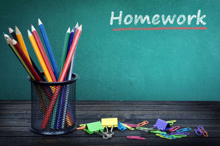 unmotivated: Homework text on green board and group of pencils Stock Photo