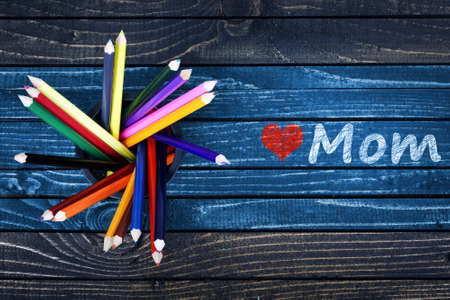Love Mom text painted and group of pencils on wooden table