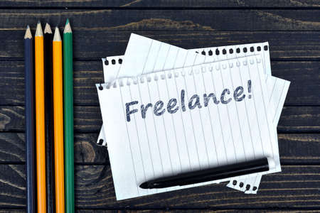 freelancing: Freelance text on notepad and office tools on wooden table