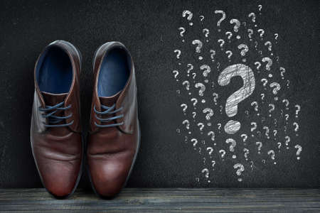 Question marks text on black board and business shoes on wooden floor