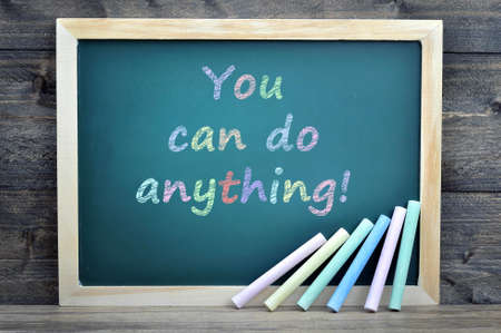 anything: You can do anything text on school board and chalk on wooden table Stock Photo