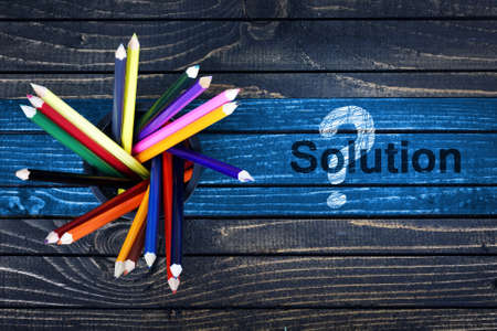 Solution text painted and group of pencils on wooden table
