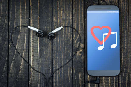 love music: Love music on phone screen and earphones on wooden table Stock Photo