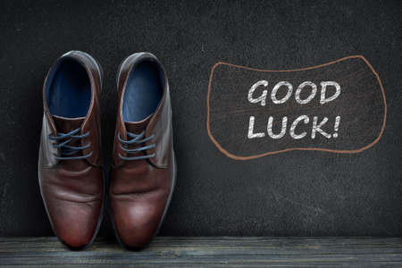 black luck: Good luck text on black board and business shoes on wooden floor Stock Photo