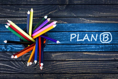 Plan B text painted and group of pencils on wooden table