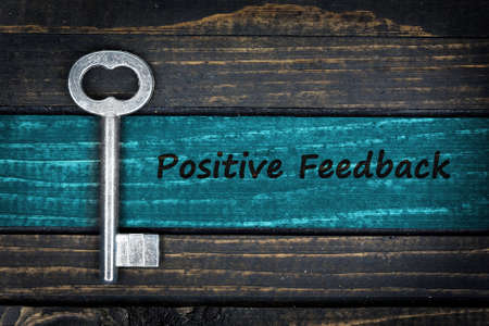 Positive Feedback word and old key on wooden table
