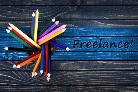freelancing: Freelance text painted and group of pencils on wooden table