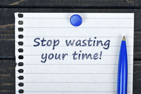 Stop wasting time text on page and pen on wooden table Stock Photo