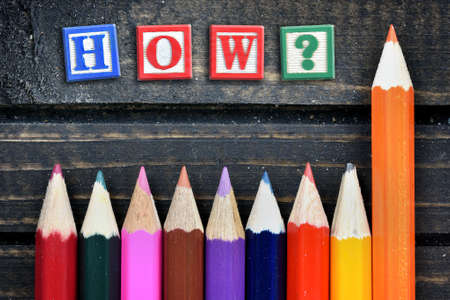 How? question text and group of pencil on wooden table Stock Photo