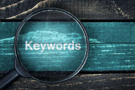 Keywords text painted and magnifying glass on wooden table