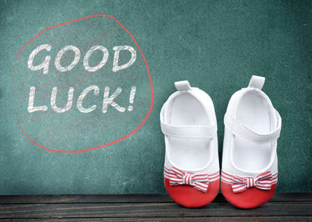 zapatos escolares: Good Luck text on school table and kid shoes Foto de archivo