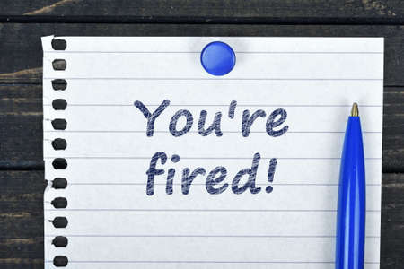 unemployed dismissed: You;re fired text on page and pen on wooden table