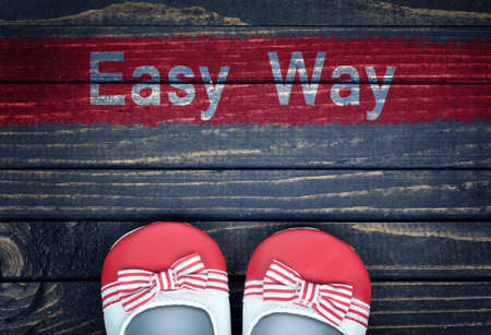 easy way: Easy Way message and kid shoes on wooden floor