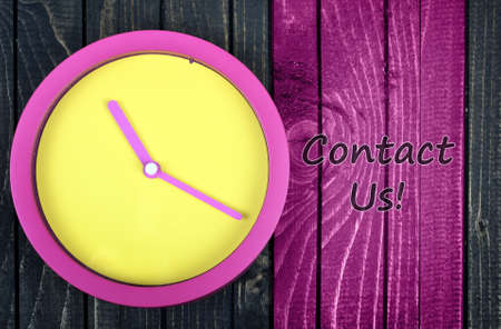 important phone call: Contact Us message and clock on wooden table