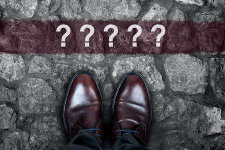 Question marks message on asphalt and business shoes Stock Photo