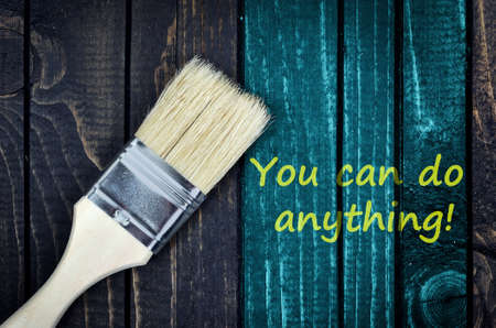 anything: You can do anything message and paintbrush on wooden wall