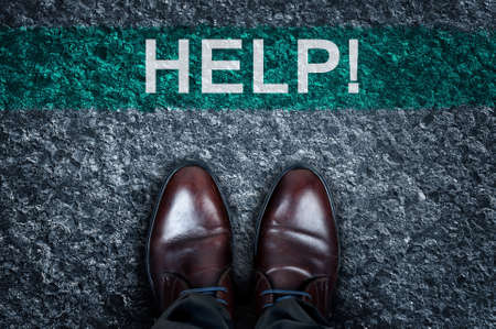 need direction: Help message on asphalt and business shoes Stock Photo