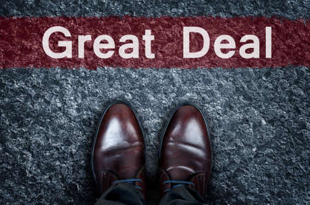 best ad: Great Deal message on asphalt and business shoes Stock Photo