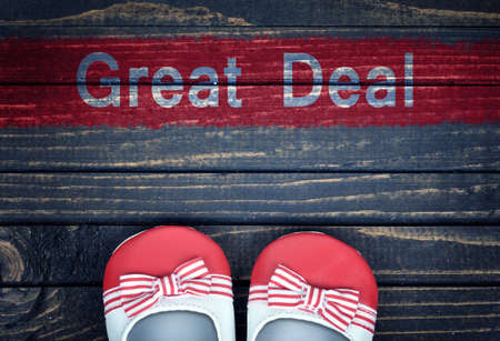 great deal: Great Deal message and kid shoes on wooden floor