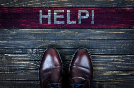 need direction: Help message and business shoes on wooden floor