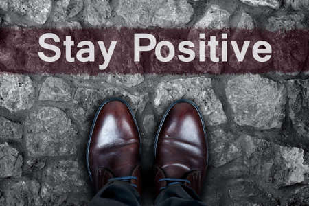 street wise: Stay positive message on asphalt and business shoes Stock Photo