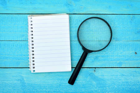 Magnifying glass and notepad on wooden table Stock Photo