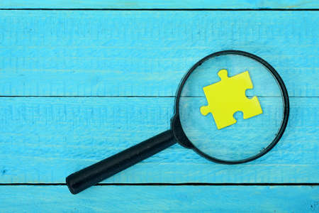 Puzzle piece and magnifying glass on wooden table Stock Photo