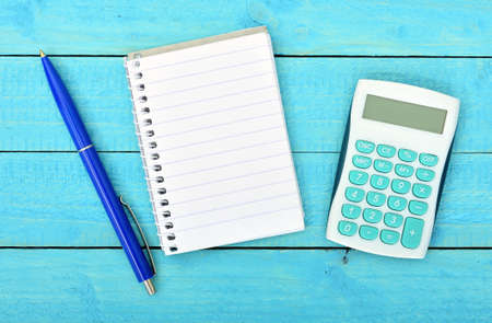 Empty notepad and calculator on wooden table