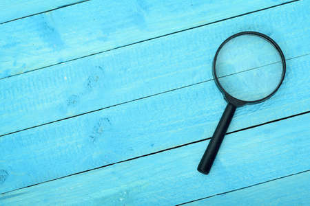 Magnifying glass on wooden table Stock Photo