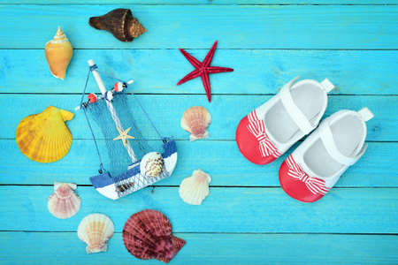 Toy ship and sea shells on blue wooden table Stock Photo