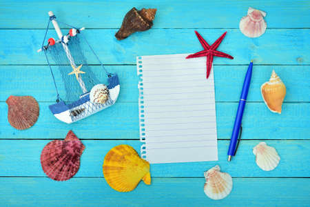 Toy ship and notepad on blue wooden table