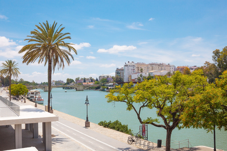 Beautiful view from the park near the Golden Tower (Torre del Oro) on the river Guadalquivir and the Triana on the backgound on blue sky and white clouds. Summer travel Stockfoto
