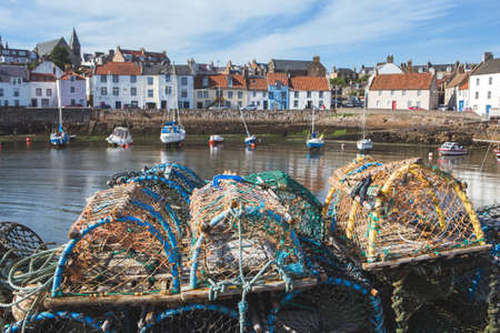 Traditional lobster pots/crab pots and small fishing boats in the East Neuk of FIfe fishing village of Pittenweem, Scotland